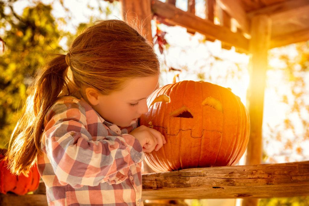 A kid and a pumpkin