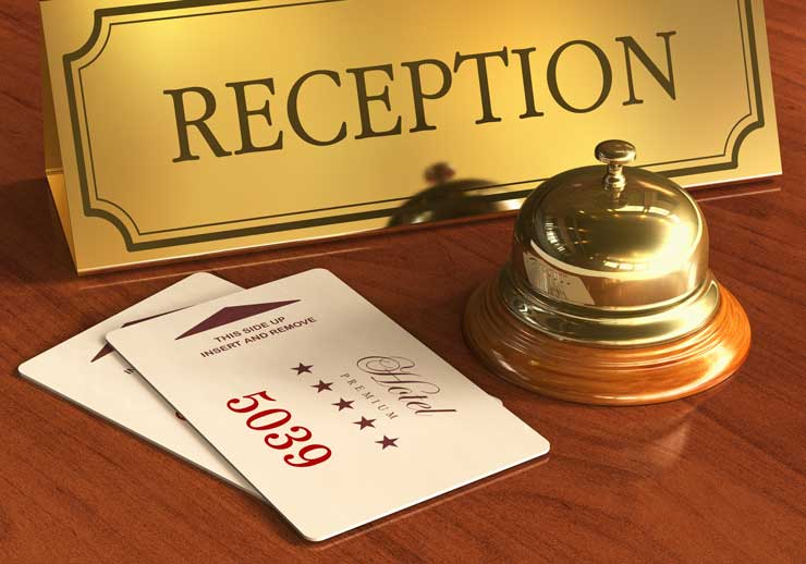 Service bell and room access cardkeys at reception desk in hotel