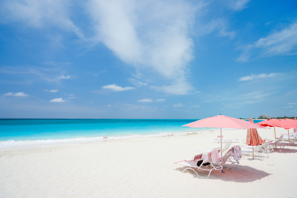 Pink umbrellas on beach at Providenciales island in Turks and Caicos